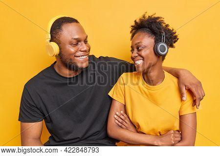 Studio Shot Of Best Friends With Dark Skin Have Pleasant Talk Smile Happily Show White Teeth Listen