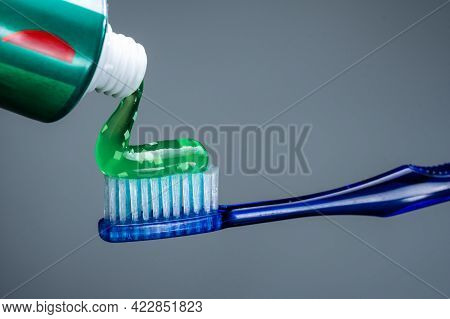 Squeeze Toothpaste Onto The Brush. Green Toothpaste On A Toothbrush. Isolate.
