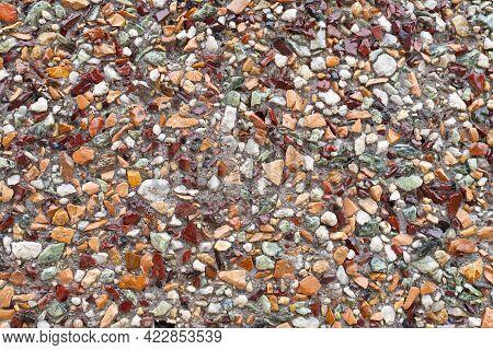 Texture. Multicolored Rubble Stones On A Concrete Base.