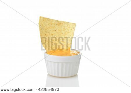 Closeup Nacho Chip Dipped In Small Bowl Of Spicy Cheese