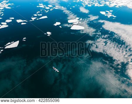 Kayak Sailing Between Ice Floes On Baikal Lake In Spring. Aerial Drone View. Sky With Clouds Reflect