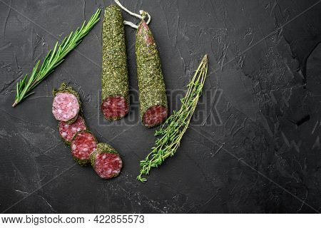 Fuet Salami Sausage In Herbs On Black Background, Top View With Copy Space.