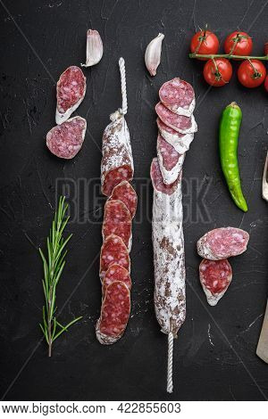 Dry Cured Fuet Salami Sausage Slices  On Balck Background, Flat Lay.