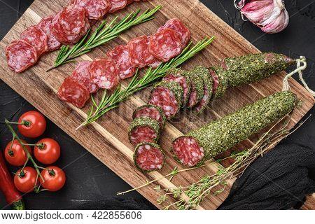 Spanish Fuet Salami Sausage Slices  On Black Textured Background.