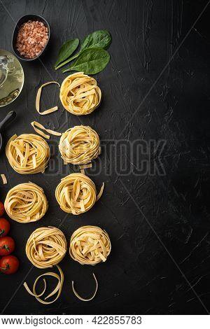 Ingredient Of Traditional Mediterranean Cuisine Uncooked Pasta Tagliatelle Set, On Black Stone Backg