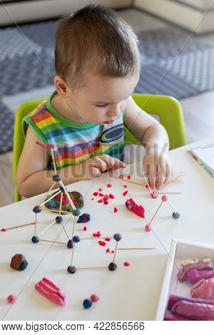 A Little Boy Sculpts From Plasticine At The Table At Home. Makes A Tower Of Toothpicks And Balls.