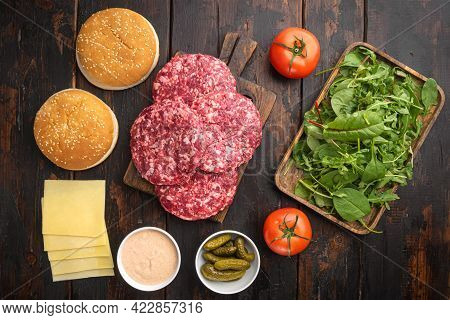 Raw Ground Beef Meat Burger Steak Cutlets And Seasonings With Buns Set, On Old Dark  Wooden Table Ba