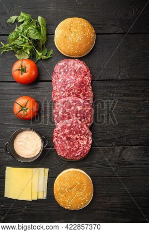 Homemade Hamburger. Raw Beef Patties, Sesame Buns With Other Ingredients Set, On Black Wooden Table