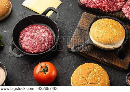 Ingredients For Cooking Burgers. Minced Beef Patties, Buns, Tomatoes, Herbs And Spices Set, On Black