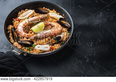 Valenciana Paella With King Prawns, Mussels And Squid On Black Background With Copy Space, Food Phot