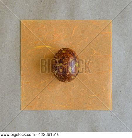 One Egg, Painted In Brown Colors, Lies On Orange Paper Napkin. Unusual Pattern On Surface Of Egg In
