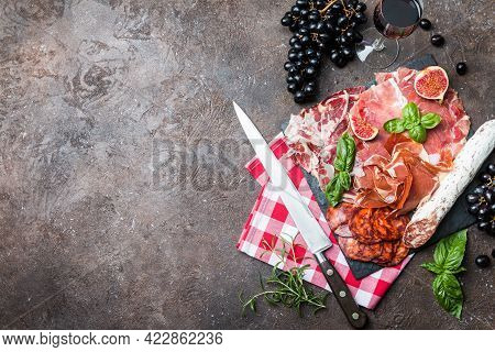 Sliced Jamon On Cutting Board With Fig , Grapes And Red Wine. Parma Ham Hamon On Wooden Background W