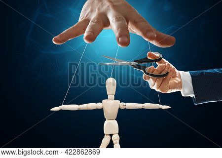 A Man's Hand Cuts The Threads Between The Puppeteer And The Puppet With Scissors. The Concept Of Lib