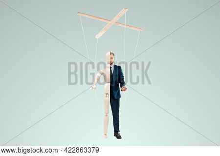 Male Hand, Puppeteer Controls The Puppet Puppet With Strings. The Concept Of Shadow Government, Worl