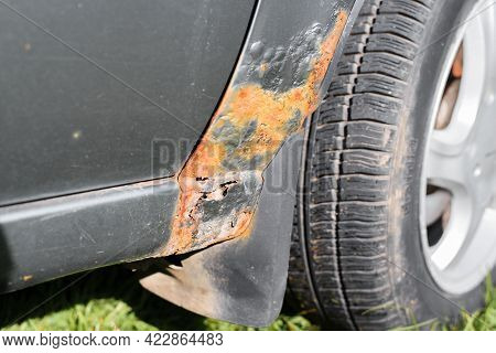 Rust And Damage To The Car Body. Metal Corrosion, Paint Decay, Holes In The Car Fender, Close-up.