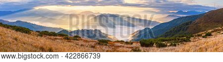 Autumn Morning Mountain Panoramic View With Sunbeams Through Haze And Low Clouds.