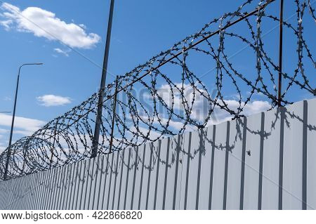 Iron Wall Against A Background Of Barbed Wire, Prison Concept, Rescue, Refugee, Lonely. Sunny Day