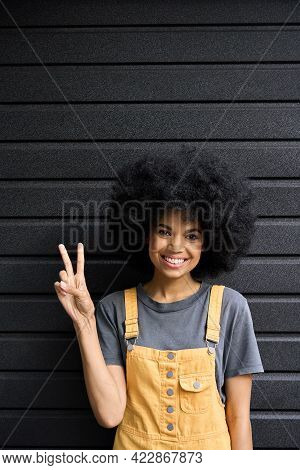 Young Beautiful Black Hipster Girl Of 20s Standing On Black Wall Background. Headshot Of Stylish Fun