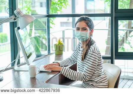 Asian Woman With Hygiene Mask Sit In Working Room In Front Of Computer And Look At Camera During Wor