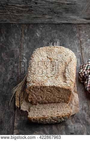 Homemade  Wholemeal Rye Bread Loaf With Sesame Seed On Wooden Table