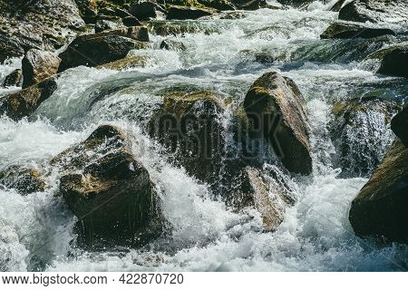 Colorful Nature Background With Big Mossy Boulders In Turbulent Flow Of Mountain River In Sunny Day.