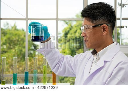 Senior Scientist With Safety Goggle Holding And Looking Blue Solvent Liquid Beaker During Research I