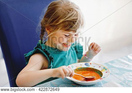 Little Preschool Girl Eating Healthy Vegetable Tomato Soup For Lunch. Cute Happy Child Taking Food A