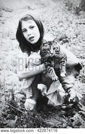 Retro Portrait Of Soviet Girl With Cat In Hands. Vintage Black And White Paper Photo. Early 1990s. O