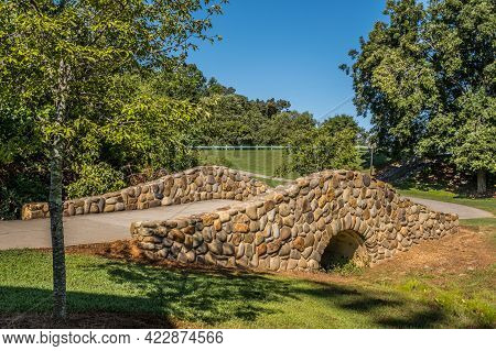 A Trail With An Old Stone Or Rock Arched Bridge That Goes Over A Creek That Flows Into The Woodlands