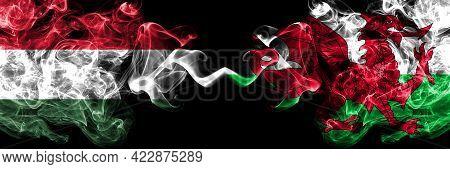 Hungary, Hungarian Vs Wales, United Kingdom Smoky Flags Side By Side.