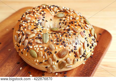 Closeup A Mouthwatering Pumpkin Seed And Sesame Bun On A Wooden Breadboard