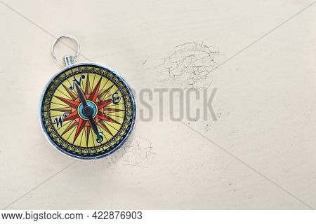 Old Classic Navigation Compass On Yellow Vintage Background With Scratches And Cracks In Paint As Sy