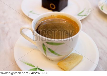 Cup Of Hot Coffee With A Sable Cookie Served On White Table