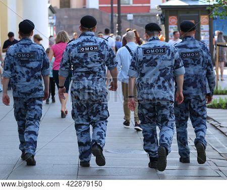 Four Russian Riot Police Officers Walk Along The City Street, Nevsky Prospekt, Saint Petersburg, Rus