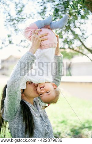 Smiling Mom Lifts Her Little Girl Upside Down And Kisses Her On The Cheek
