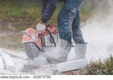 Worker Mason Cuts The Sidewalk Tile With Circular Saw While Repairing Sidewalk In City Street.