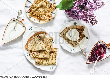 Cozy Homemade Breakfast On A Light Background - Wholegrain Crepes, Cranberry Jam, Lilac Bouquet, Top