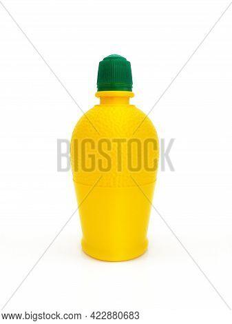 Close Up Of Bottle Of Squeezed Lemon Juice Dressing. Lemon Juice In An Open Bottle On A White Backgr