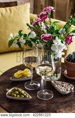 Aperitif Set. Two Glasses Of White Wine And A Variety Of Snacks Olives, Pistachios, Potatoes Chips O