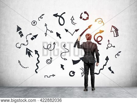 Office Man In Black Suit Holding Pen, Writing Multiple Lines And Arrows With Different Direction, Co