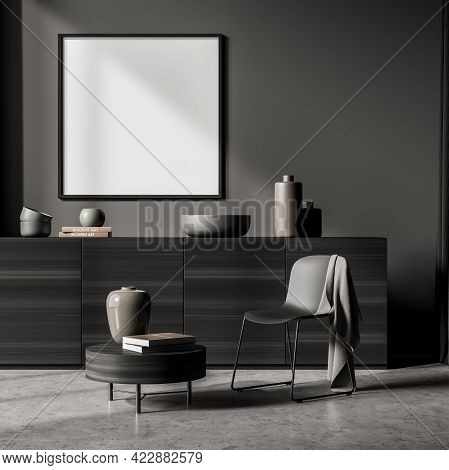 Relaxing Room Interior With Grey Commode And A Black Chair, Coffee Table With Books On Grey Concrete