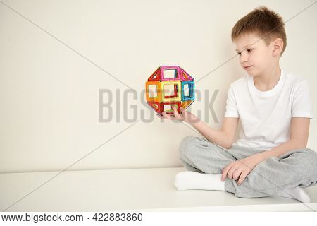Boy Plaing In A Magnetic Colorfull Constructor. A Schoolboy Makes A Model Of The Earth From A Magnet
