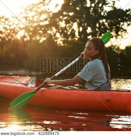 Side View Of Focused Young Woman Holding A Paddle While Kayaking In A Lake Surrounded By Nature On A