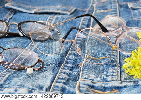 Eye Glasses On A Denim Jacket, An Old Jacket Made Of Blue Jeans And Multiple Eyes Glasses, Trendy Ey