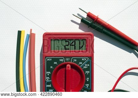 Multimeter With Text On Display 24 V And Heat Shrink Insulation On White Background. Construction An