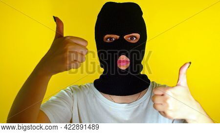 Close Up Of Unrecognizable Woman In Black Balaclava Showing Thumbs Up On Yellow Background. Unknown