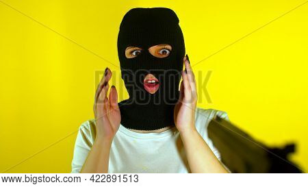 Unrecognizable Woman In Pink Balaclava With Gun On Yellow Background. Dangerous Criminal In Mask Wit
