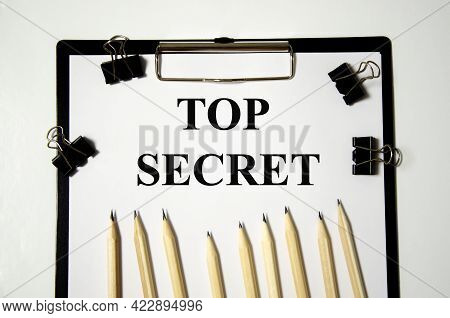 Top Secret The Word Is Written On A White Piece Of Paper With Pencils. Text
