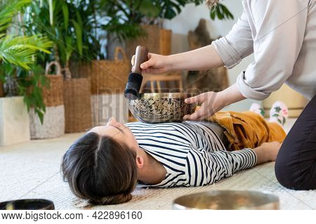 Young Female Having Tibetan Massage, Singing Bowl Therapy With Traditional Tibet Cymbals At Home. Ca