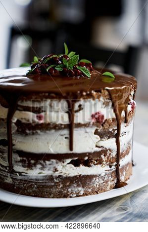 Chocolate Brownie Cake With Cherries And Mint Leaves. Close Up
